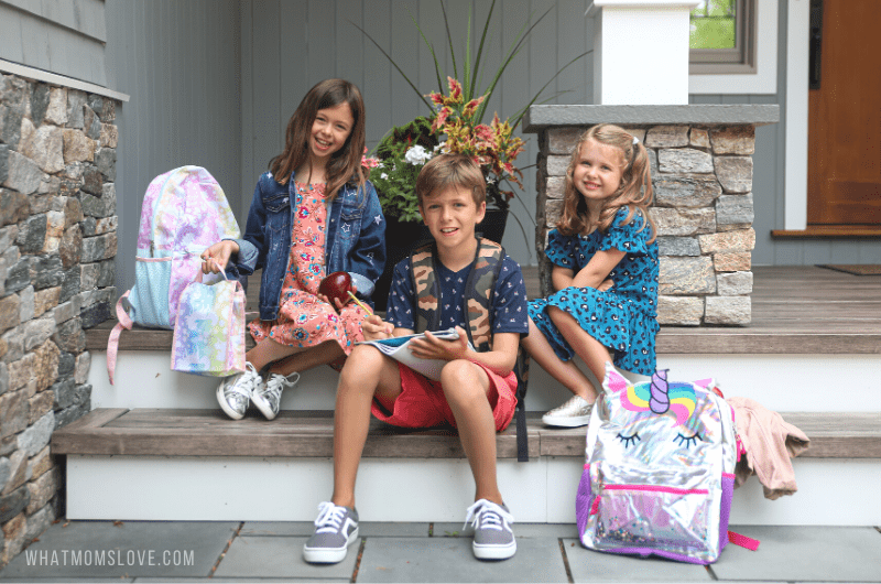 3 kids sitting on steps on first day of school