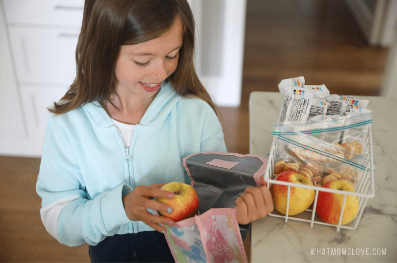 young girl packing lunch for school
