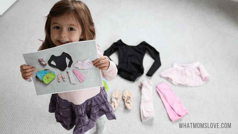 young girl holding up photo of clothes as if getting ready to pack a bag