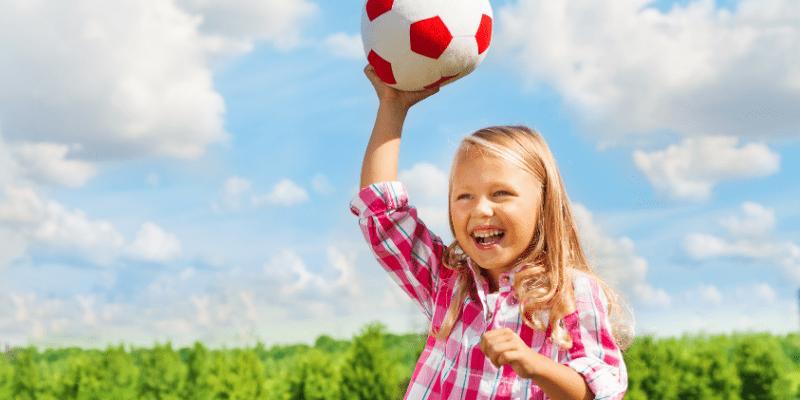 girl laughing holding soccer ball